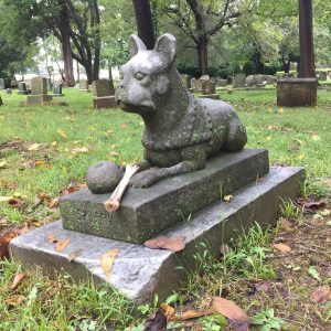 Dog statue at pet cemetery with bone. Photo by Julianne Mangin, Sept 2018